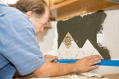 L'operaio delle mattonelle imposta le mattonelle immagine stock
