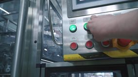 L'operaio preme il bottone sul punto di controllo ed inizia il trasportatore della linea di produzione, primo punto di vista dell video d archivio