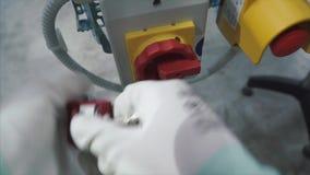 L'operaio preme il bottone sul punto di controllo ed inizia il trasportatore della linea di produzione, primo punto di vista dell archivi video