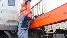 L'operatore in casco determina l'asta della gru con le leve video d archivio