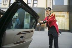 L'operatore d'appoggio in campana in rivestimento rosso apre la porta del limo davanti all'hotel del vicolo del parco di Helmsley immagini stock