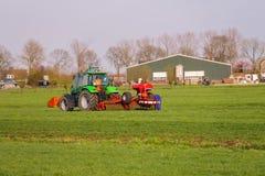 L'operatore del trattore sul trattore effettua il lavoro di campo Fotografie Stock
