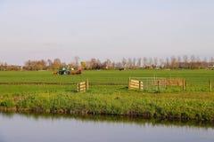 L'operatore del trattore sul trattore effettua il lavoro di campo Immagini Stock Libere da Diritti