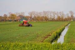 L'operatore del trattore sul trattore effettua il lavoro di campo Immagine Stock