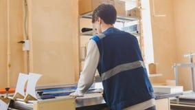 L'operatore della stamperia lavora alla macchina tipografica Fotografia Stock Libera da Diritti
