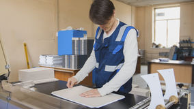L'operatore della stamperia lavora alla macchina tipografica Fotografia Stock