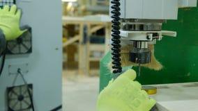 L'operatore di una macchina per la lavorazione del legno moderna di CNC procede agli adeguamenti prima di lavoro Cambia la taglie fotografia stock libera da diritti