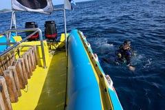 L'operatore subacqueo galleggia in acqua vicino alla barca bianco-blu Fotografie Stock