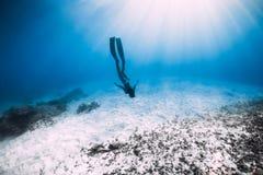 L'operatore subacqueo libero della giovane donna scivola sopra il mare sabbioso con le alette fotografia stock