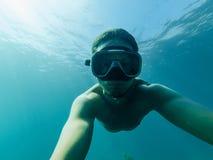L'operatore subacqueo maschio nuota in mare sotto l'acqua con una maschera e una presa d'aria Immagini Stock Libere da Diritti