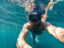 L'operatore subacqueo maschio nuota nel mare sotto l'acqua blu con una maschera e una presa d'aria Fotografie Stock