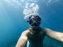 L'operatore subacqueo maschio nuota nel mare sotto l'acqua con una maschera e una presa d'aria Immagini Stock Libere da Diritti