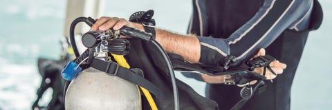 L'operatore subacqueo prepara la sua attrezzatura per tuffarsi l'INSEGNA del mare, formato lungo fotografie stock