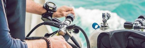 L'operatore subacqueo prepara la sua attrezzatura per tuffarsi l'INSEGNA del mare, formato lungo immagine stock libera da diritti