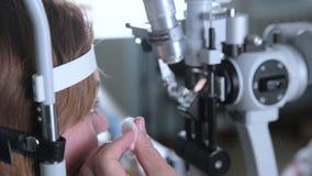 L'ophtalmologue vérifie les yeux de la femme banque de vidéos