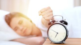 L'opposé de réveil de la jeune femme somnolente étirant la main au disposé de sonnerie d'alarme l'arrêtent Réveillez-vous tôt, pa image libre de droits