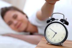 L'opposé de réveil de la jeune femme somnolente étirant la main au disposé de sonnerie d'alarme l'arrêtent Réveillez-vous tôt, pa images stock