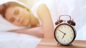 L'opposé de réveil de la jeune femme somnolente étirant la main au disposé de sonnerie d'alarme l'arrêtent Réveillez-vous tôt, pa photographie stock libre de droits