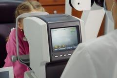 L'optométriste examine la vue la petite fille photo stock