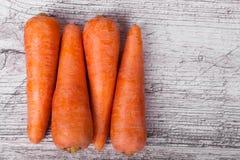 L'orange a épluché la carotte, régénérant des légumes pour les plats savoureux, les smoothies, gâteaux sur un fond en bois clair  photo libre de droits