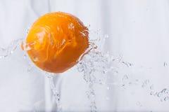 L'orange est lâchée dans l'éclaboussure de l'eau Photographie stock