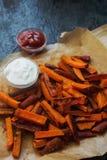 L'orange faite maison a fait des fritures cuire au four de patate douce avec de la sauce et le ketchup à crème sure Mode de vie s Photographie stock libre de droits