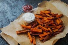 L'orange faite maison a fait des fritures cuire au four de patate douce avec de la sauce et le ketchup à crème sure Mode de vie s Image stock