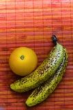 L'orange juteuse avec deux a tacheté des bananes sur un fond rose de tapis de rotin L'espace négatif pour le texte Photographie stock