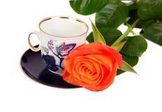 L'orange s'est levée avec la tasse bleue de coffe Photos stock