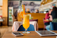 L'orangeade, comprimé, smartphone s'est étendue sur la table en café Image stock