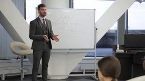 L'orateur masculin explique les investissements dans la devise numérique sur la conférence d'affaires banque de vidéos