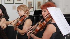 L'orchestra del primo piano dei violinisti gioca la musica classica e lo sguardo in strato di carta con le note musicali stock footage
