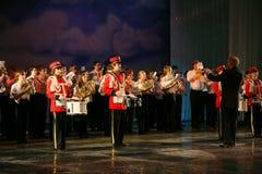 L'orchestre des enfants consolidés du palais de la créativité de la jeunesse et de l'exposition des batteurs dans l'uniforme mili Image libre de droits