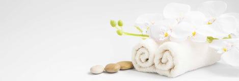 L'orchidea della stazione termale con gli asciugamani molli ed il massaggio lapida la regolazione Immagini Stock