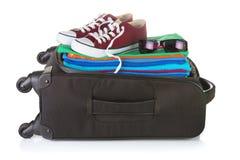 L'ordinaire a roulé la valise noire emballée avec l'été lumineux vêtent Photographie stock libre de droits