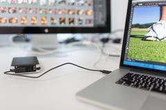 L'ordinateur de photographes avec la photo éditent des apps/fonctionnement de programmes photos libres de droits