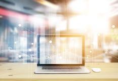 L'ordinateur portable avec des bourses mondiales d'icônes graphiques connectent sur l'écran dans le bureau Photographie stock