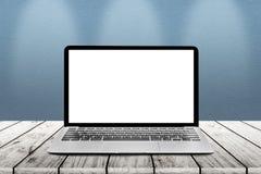 L'ordinateur portable avec l'écran vide blanc de maquette est sur les WI en bois de table Photo libre de droits