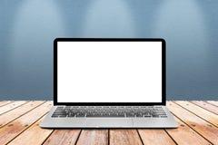 L'ordinateur portable avec l'écran vide blanc de maquette est sur les WI en bois de table Images stock