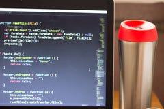 L'ordinateur portable avec le code et le rouge de programmation de Web a couvert le flacon de côté Photos libres de droits