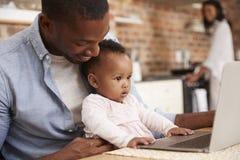L'ordinateur portable d'utilisation d'And Baby Daughter de père comme mère prépare le repas photo libre de droits
