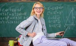 L'ordinateur portable de prise de professeur de femme reposent le fond de tableau de salle de classe de table Professeur de génér photographie stock