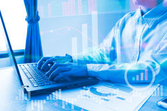 L'ordinateur portable fonctionnant de personnes dans le graphique de siège social du marché boursier t Photo libre de droits