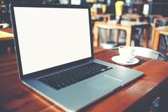 L'ordinateur portable portatif et la tasse de café se trouvant sur une table en bois en café barrent l'intérieur Images stock