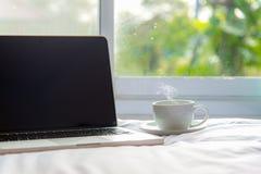 L'ordinateur portable travaillant au lit et au café blancs dans la fenêtre le jour pluvieux, vacances fraîches de matin Image libre de droits