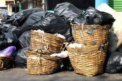 L'ordure en plastique de rebut dans le panier, paniers en bambou de rotin de déchets de pile met en sac sur le plancher et beauco photo stock