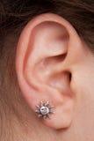 L'oreille des femmes avec une boucle d'oreille photographie stock libre de droits