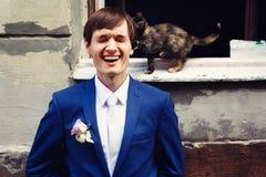 L'oreille du petit de chat fiancé de cathes tandis qu'il tient derrière les WI ouverts Photos libres de droits