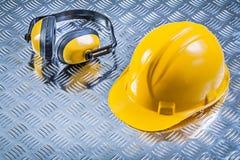 L'oreille protectrice rate le casque antichoc sur le constru cannelé de fond en métal photo libre de droits