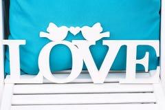 L'oreiller bleu sur la chaise blanche et le mot en bois AIMENT Photographie stock